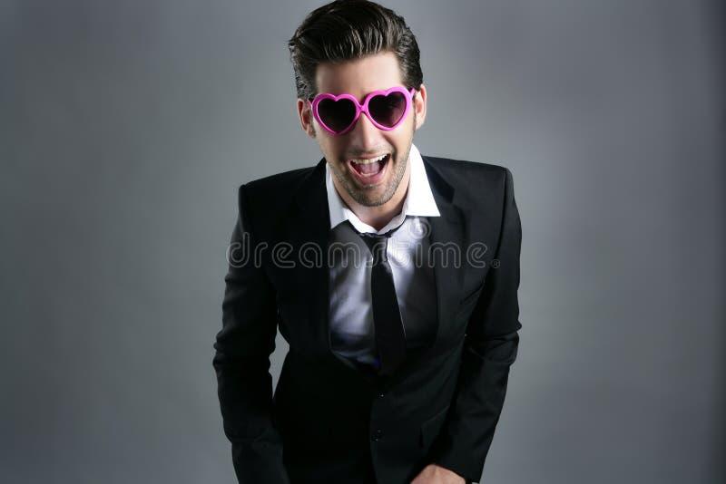 Hombre de negocios divertido de las gafas de sol del color de rosa de la dimensión de una variable del corazón imagenes de archivo