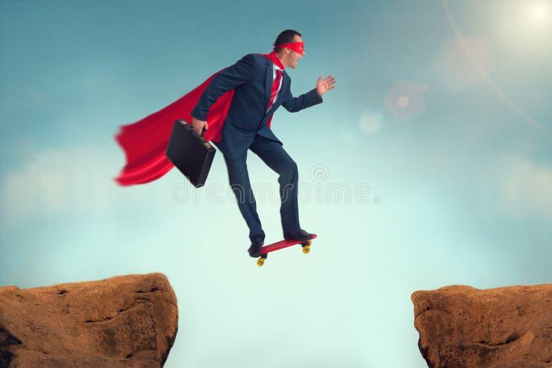 Hombre de negocios divertido del super héroe en un monopatín imagen de archivo
