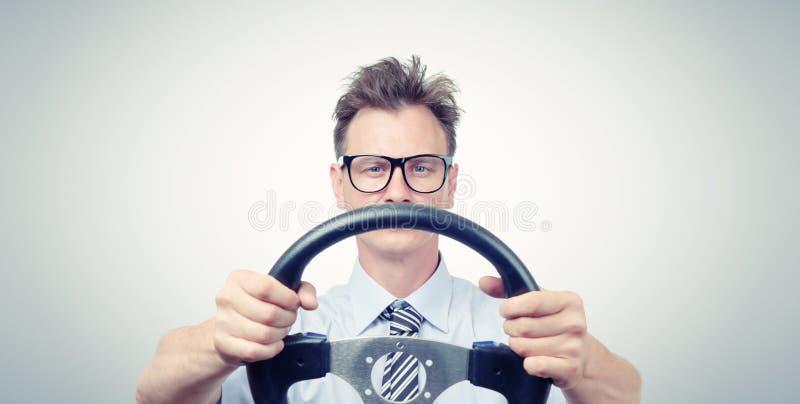 Hombre de negocios divertido en los vidrios con un volante, concepto de la impulsión del coche foto de archivo libre de regalías