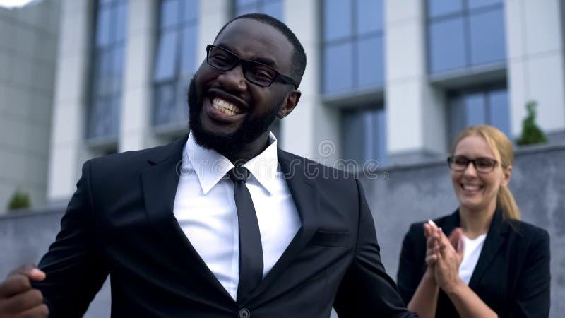 Hombre de negocios divertido feliz de conseguir la promoción, celebrando éxito, ayuda del equipo imagen de archivo libre de regalías