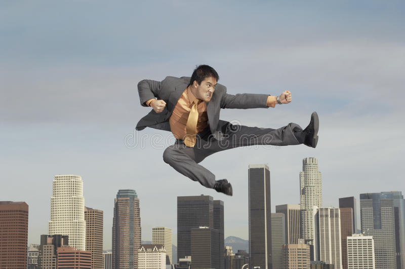 Hombre de negocios Doing Martial Arts contra paisaje urbano imagen de archivo