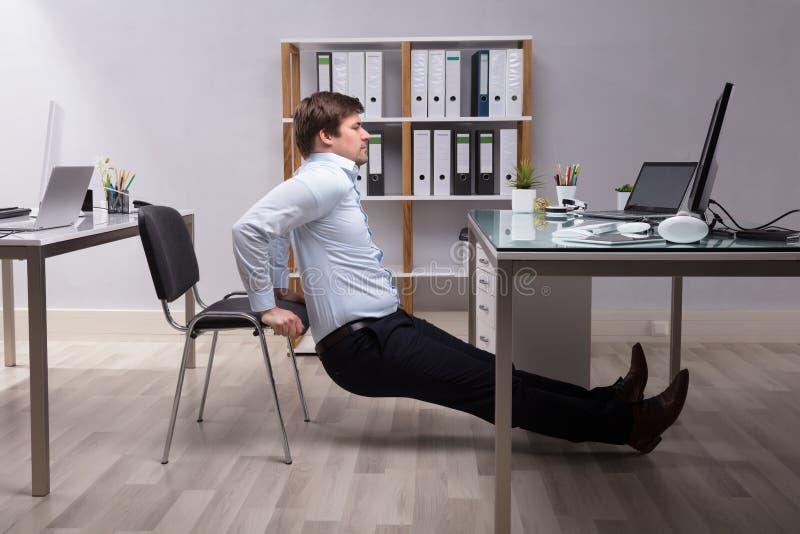 Hombre de negocios Doing Triceps Dips en oficina foto de archivo
