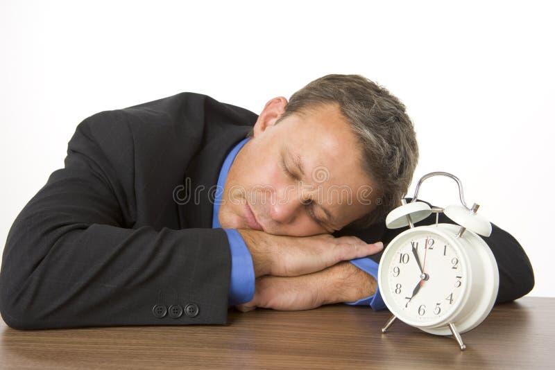 Hombre de negocios dormido en el escritorio por un reloj de alarma imágenes de archivo libres de regalías