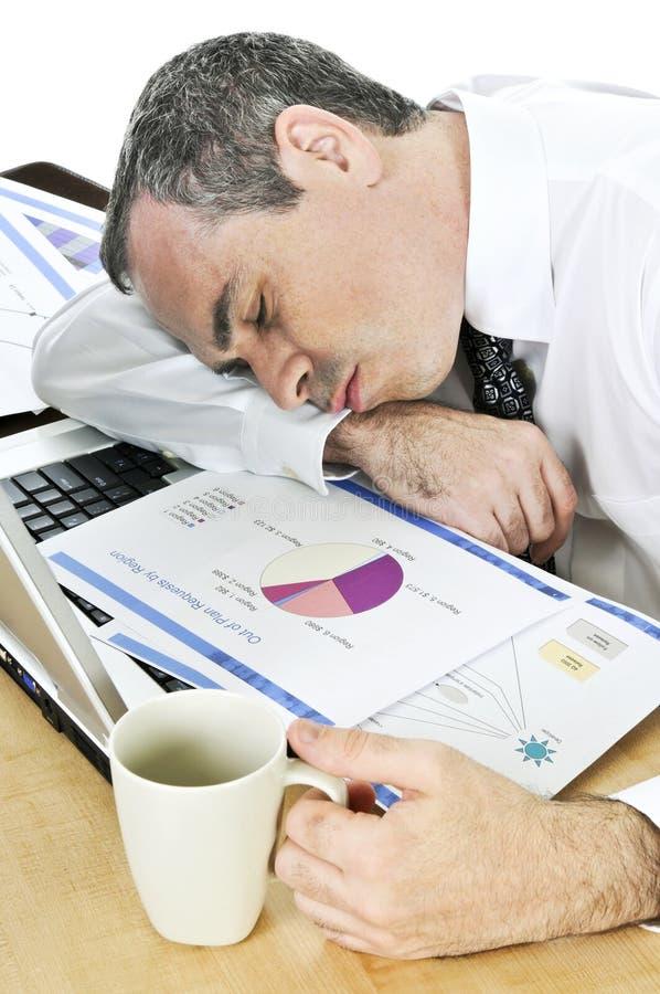 Hombre de negocios dormido en su escritorio en el fondo blanco imagen de archivo
