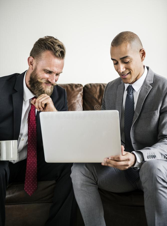 Hombre de negocios dos que se sienta en un sofá que trabaja en el ordenador portátil fotografía de archivo libre de regalías