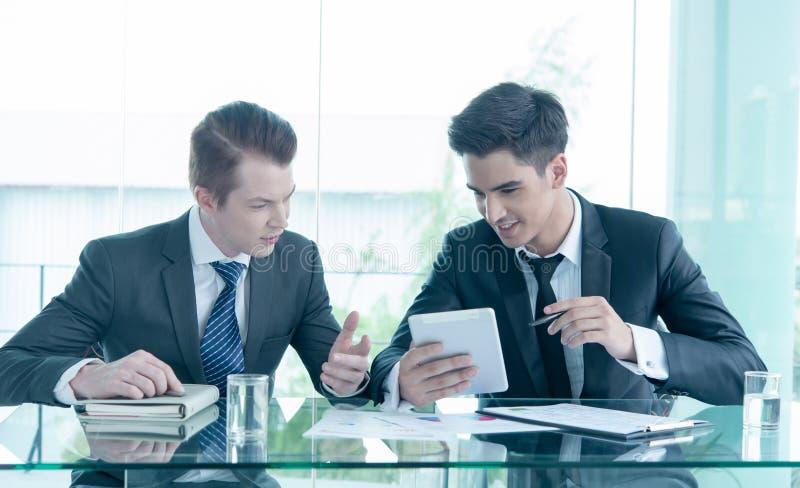 Hombre de negocios dos usando la tableta en la reunión fotografía de archivo libre de regalías