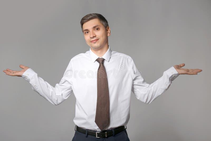 Hombre de negocios dudoso en fondo gris fotos de archivo libres de regalías