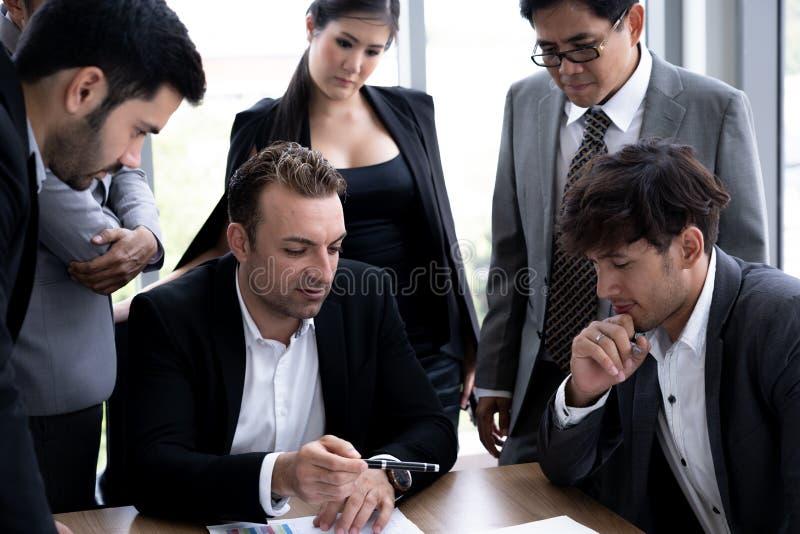 Hombre de negocios ejecutivo en la reunión de grupo con otros empresarios imagen de archivo