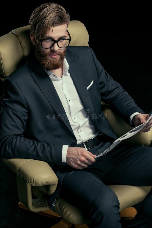 Hombre de negocios elegante en las lentes que sostienen el periódico fotos de archivo libres de regalías