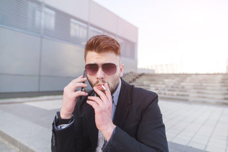 Hombre de negocios elegante que habla en el teléfono y que fuma un cigarrillo foto de archivo