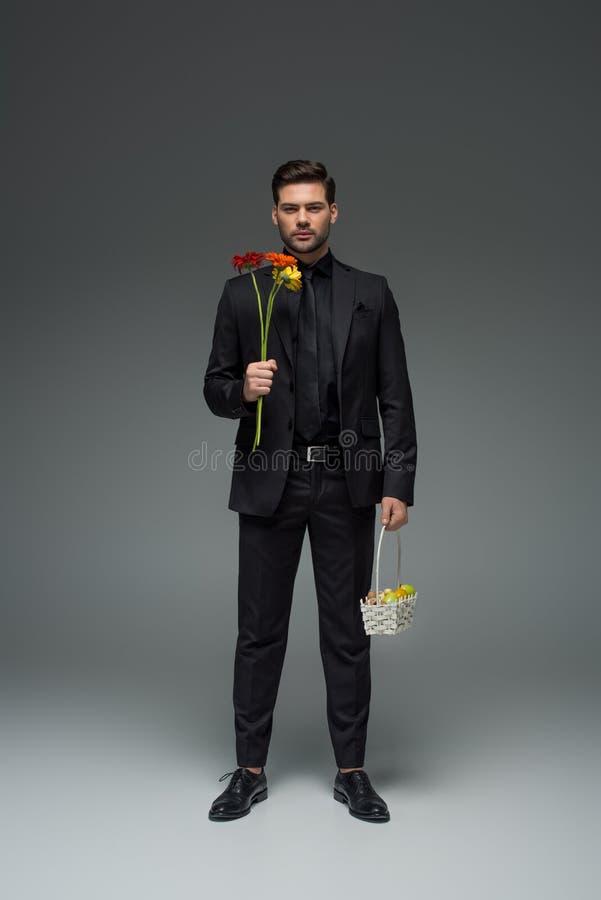 Hombre de negocios elegante que sostiene las flores y la cesta con las frutas en el gris, para mujer internacional imagenes de archivo