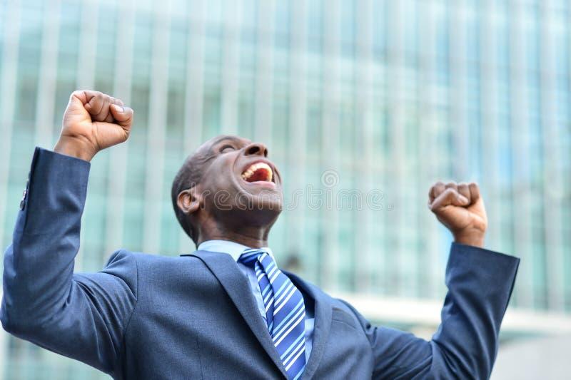 Hombre de negocios emocionado que aumenta sus brazos fotografía de archivo
