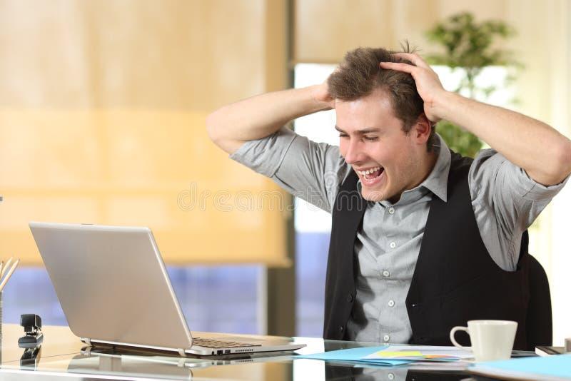 Hombre de negocios emocionado que comprueba el contenido del ordenador portátil en la oficina foto de archivo