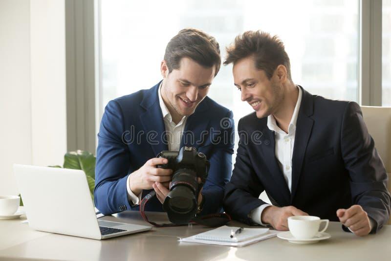Hombre de negocios emocionado que sostiene la cámara profesional, mostrando el photogr imagen de archivo