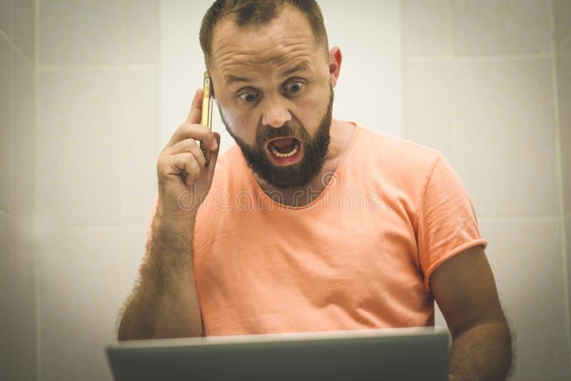 Hombre de negocios emocionado que trabaja en el ordenador portátil y que habla en el teléfono asentado en el retrete foto de archivo libre de regalías