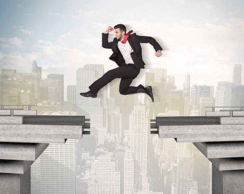 Hombre de negocios enérgico que salta sobre un puente con hueco fotos de archivo
