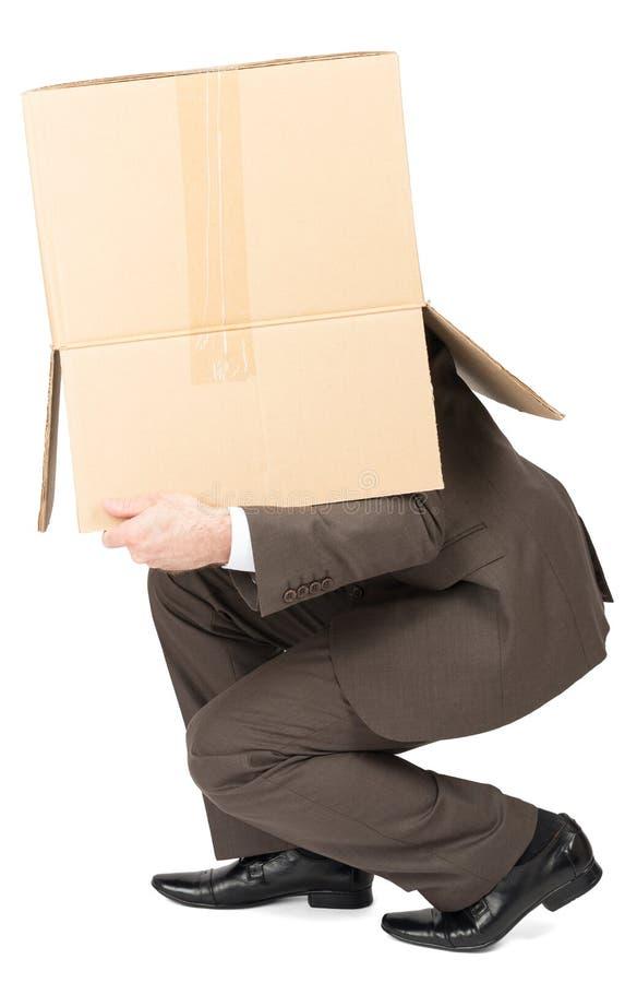 Hombre de negocios en caja del cartón del traje que lleva en la cabeza fotografía de archivo