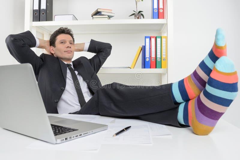 Hombre de negocios en calcetines enrrollados. Hombre de negocios confiado que sostiene su le imágenes de archivo libres de regalías
