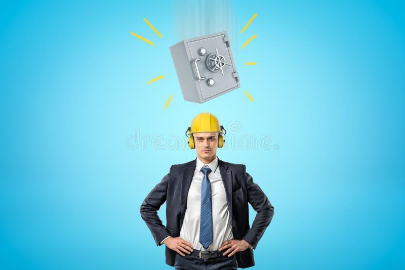 Hombre de negocios en casco amarillo con los protectores contra el ruido, colocándose con las manos en caderas, y la caja fuerte  imagenes de archivo