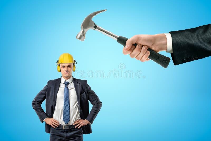 Hombre de negocios en casco amarillo con los protectores contra el ruido, colocándose con las manos en caderas, y el martillo de  fotografía de archivo libre de regalías