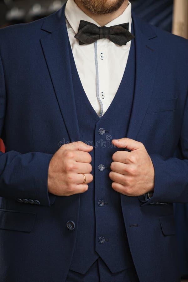 Hombre de negocios en chaleco clásico contra la fila de trajes en tienda Un hombre elegante joven en una chaqueta negra del paño  fotos de archivo libres de regalías