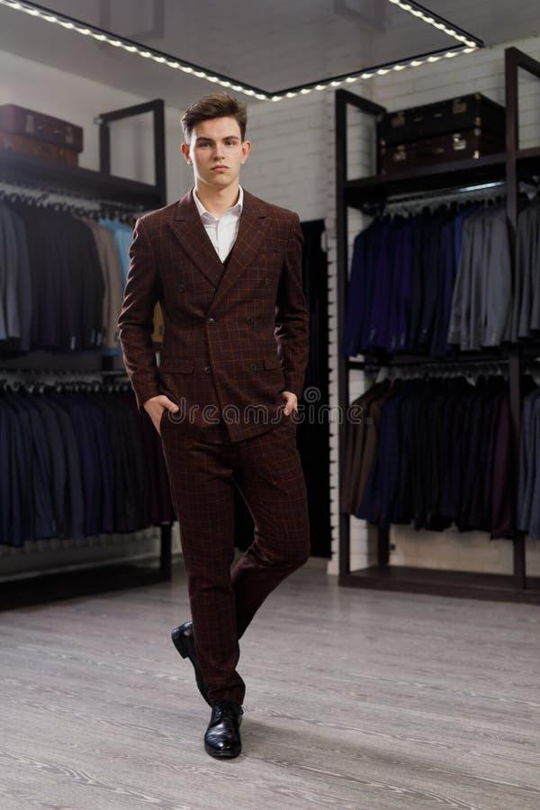 Hombre de negocios en chaleco clásico contra la fila de trajes en tienda Un hombre elegante joven en una chaqueta Está en la sala fotografía de archivo