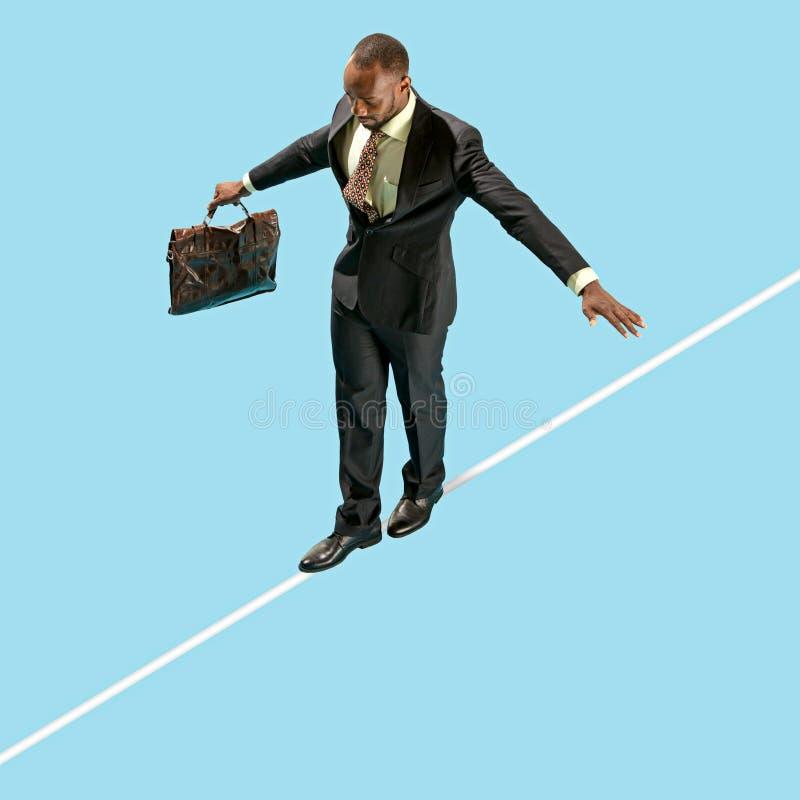 Hombre de negocios en concentrado de la cuerda tirante a caminar aislado en fondo azul imágenes de archivo libres de regalías