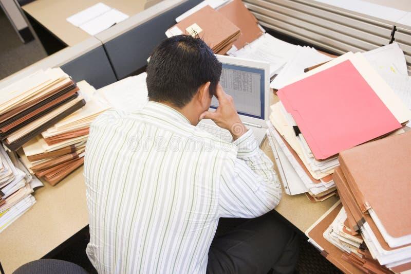 Hombre de negocios en cubículo con la computadora portátil foto de archivo