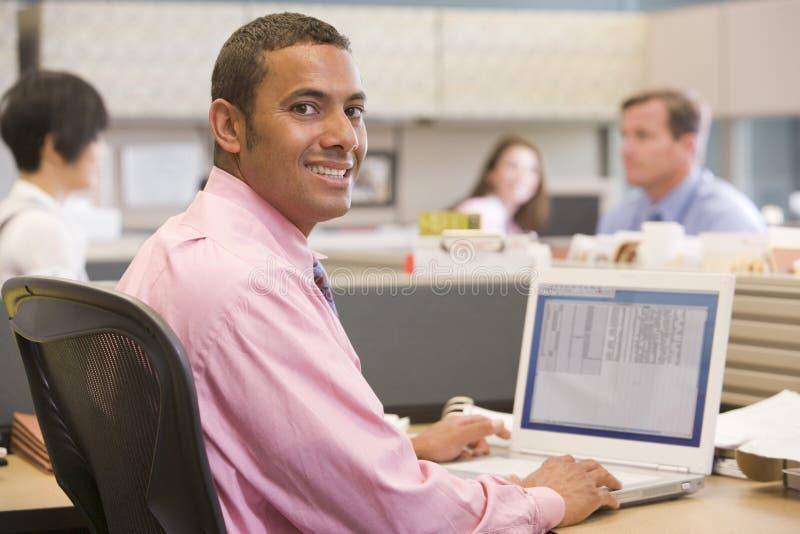 Hombre de negocios en cubículo con la sonrisa de la computadora portátil foto de archivo libre de regalías