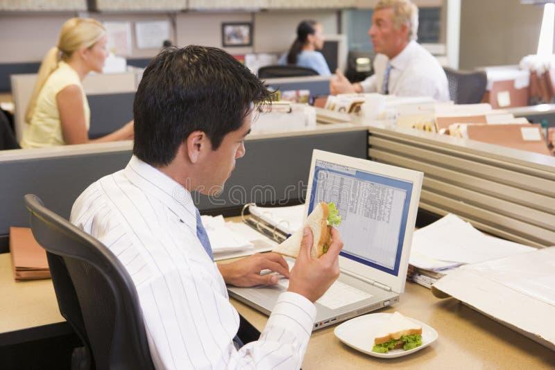 Hombre de negocios en cubículo en la computadora portátil que come el emparedado fotos de archivo libres de regalías