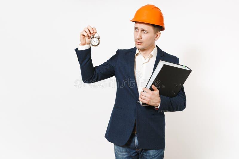 Hombre de negocios en cuestión joven en el traje oscuro, el casco de protección protector sosteniendo la carpeta negra para el do fotos de archivo libres de regalías