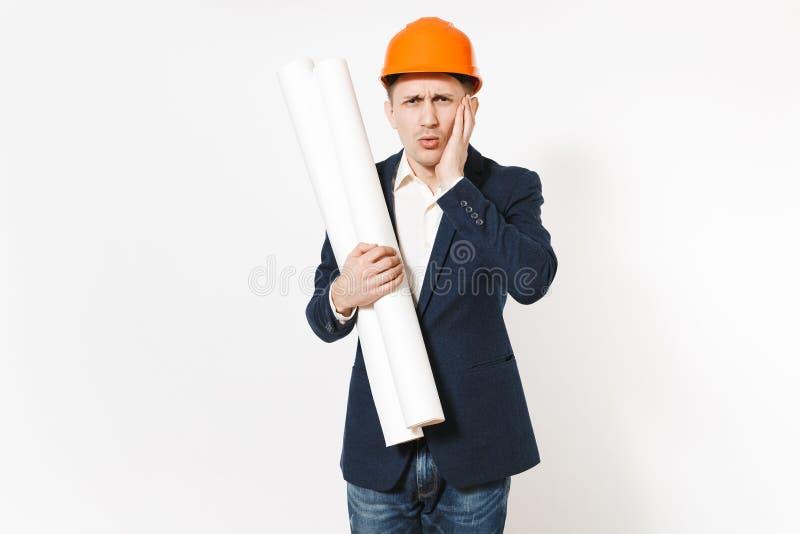 Hombre de negocios en cuestión joven en el traje oscuro, casco protector de la construcción que lleva a cabo planes de los modelo fotos de archivo libres de regalías