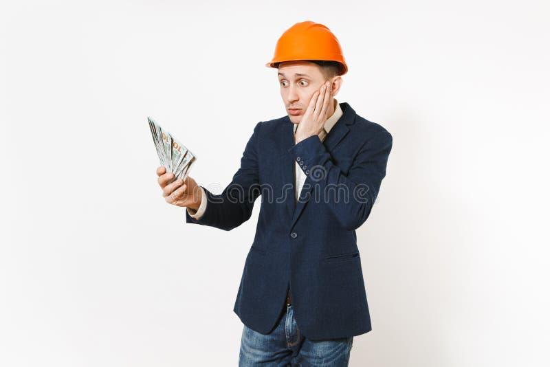 Hombre de negocios en cuestión joven en traje oscuro, paquete protector de la tenencia del casco de protección de dólares, dinero imágenes de archivo libres de regalías