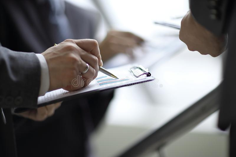 Hombre de negocios en el control de la programación un informe financiero y señalar en una carta de barra con una pluma fotografía de archivo libre de regalías