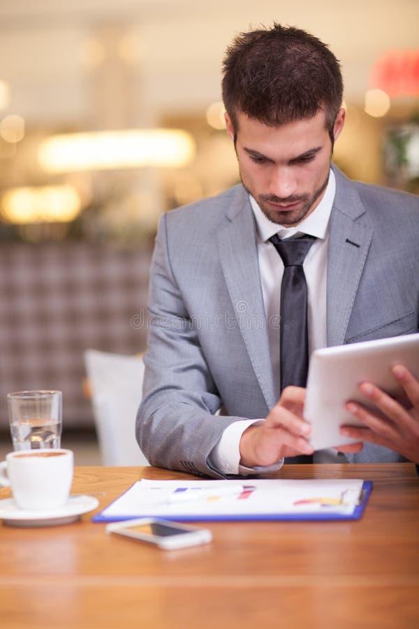 Hombre de negocios en el descanso para tomar café que trabaja en su ipad imágenes de archivo libres de regalías