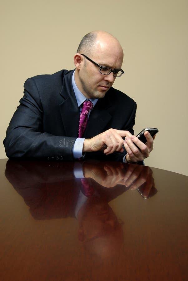 Hombre de negocios en el escritorio con el teléfono fotos de archivo