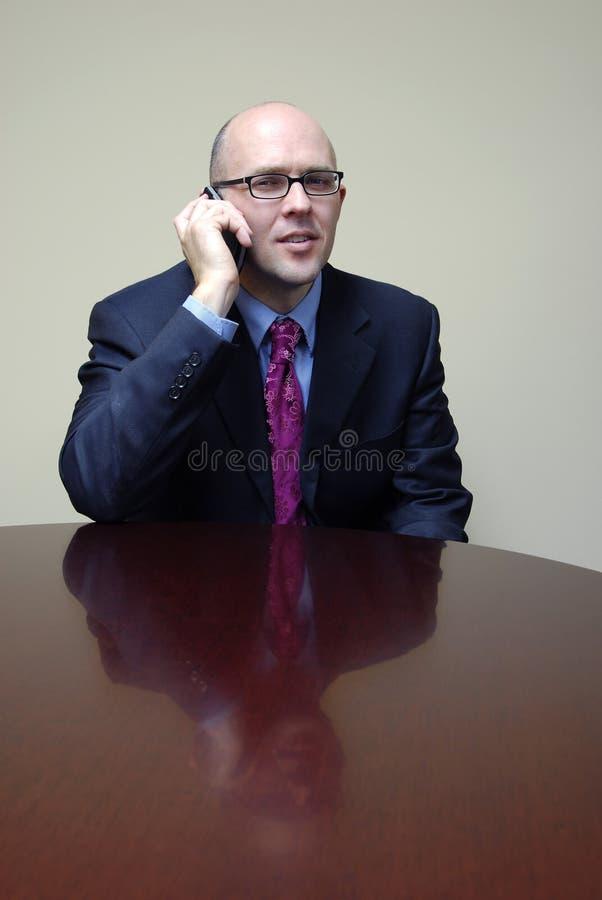 Hombre de negocios en el escritorio con el teléfono fotos de archivo libres de regalías
