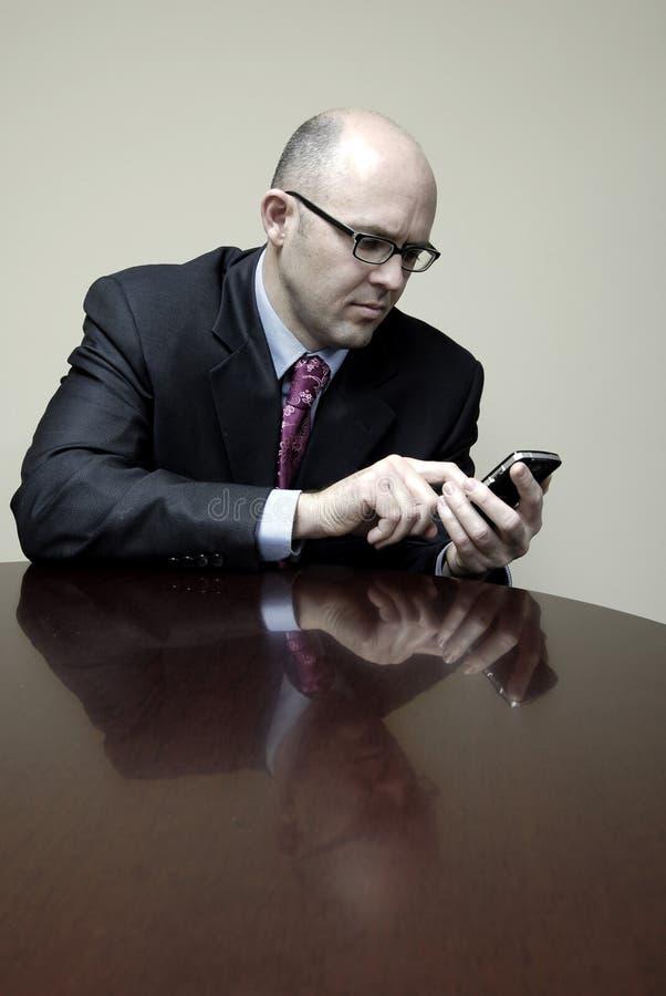 Hombre de negocios en el escritorio con el teléfono celular que termina la transacción fotos de archivo
