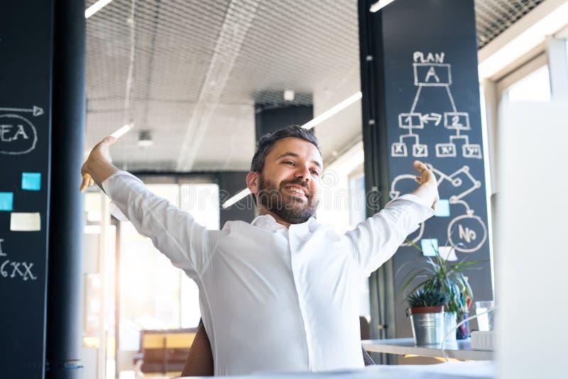 Hombre de negocios en el escritorio en su oficina que estira los brazos foto de archivo libre de regalías