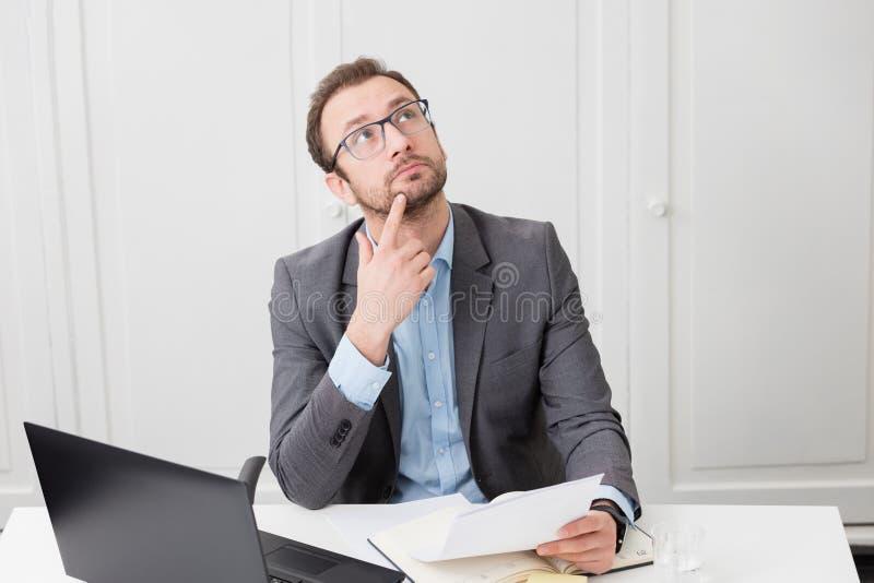 Hombre de negocios en el escritorio, mirando para arriba y pensando imágenes de archivo libres de regalías