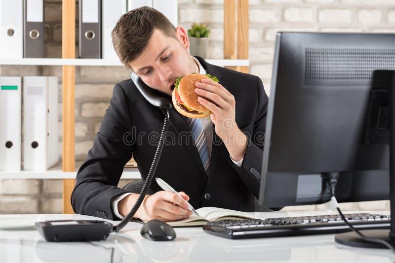Hombre de negocios en el escritorio que come la hamburguesa y el trabajo foto de archivo