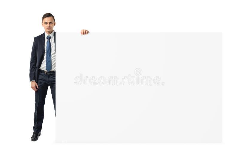 Hombre de negocios en el fondo blanco que lleva a cabo una tablilla de anuncios en blanco de la hombro-altura imágenes de archivo libres de regalías