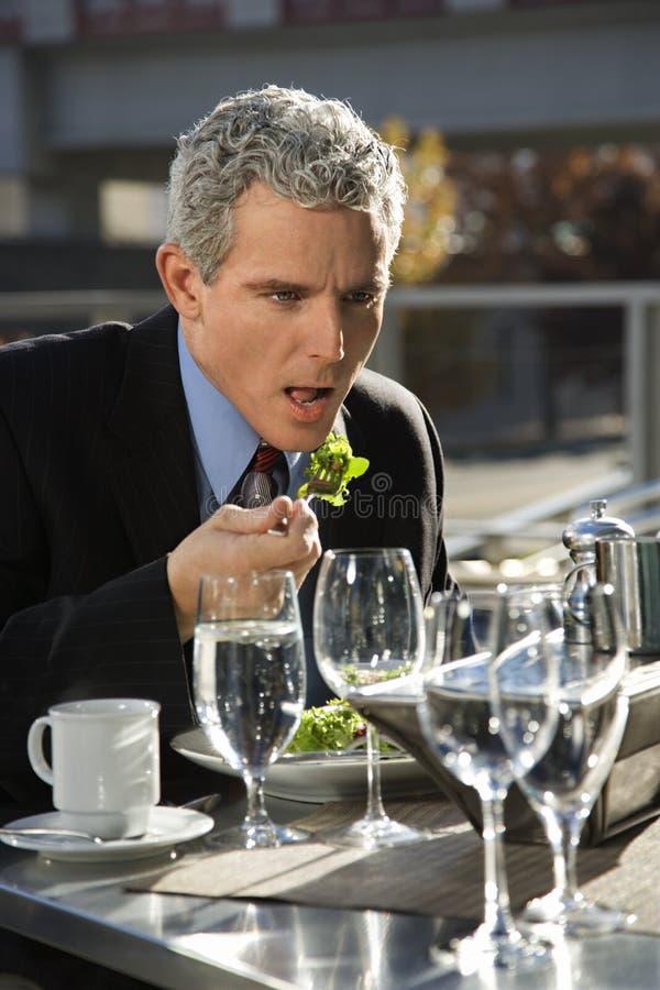 Hombre de negocios en el juego que se sienta en el vector de patio exterior que come la ensalada. foto de archivo libre de regalías
