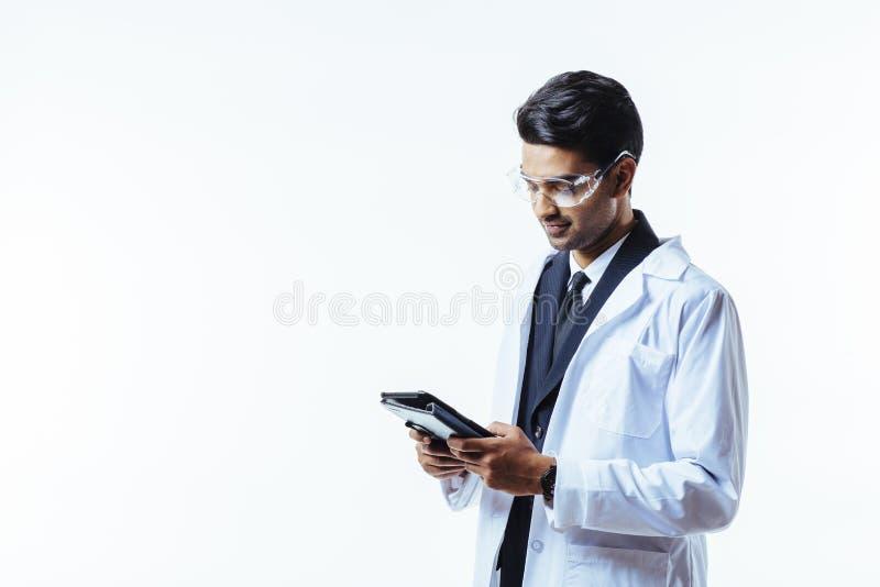 Hombre de negocios en el labcoat que mira la tableta fotos de archivo
