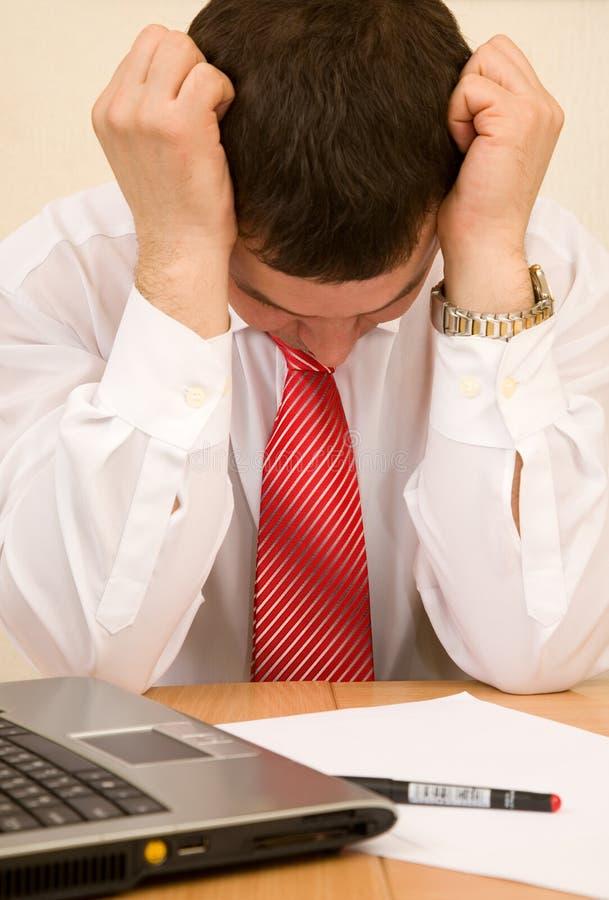 Hombre de negocios en el lugar de trabajo que piensa o que siente cansado imágenes de archivo libres de regalías