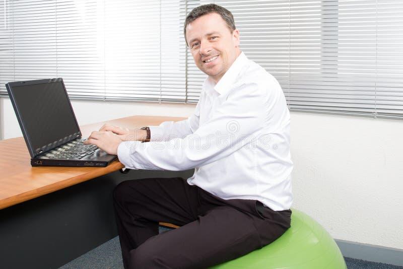 hombre de negocios en el ordenador portátil de trabajo de la bola de la estabilidad fotografía de archivo