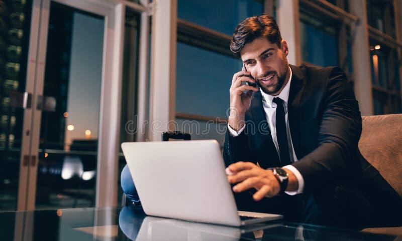 Hombre de negocios en el salón que espera del aeropuerto usando el ordenador portátil y el pH móvil fotografía de archivo libre de regalías