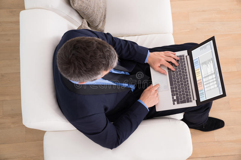 Hombre de negocios en el sofá usando el ordenador portátil imagen de archivo libre de regalías