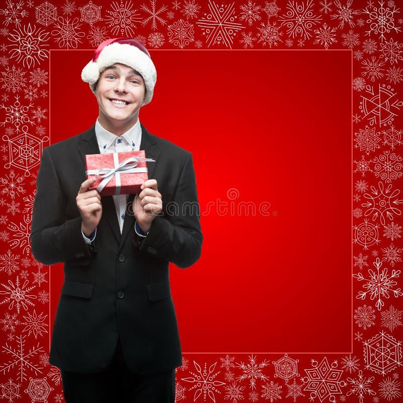 Hombre de negocios en el sombrero de santa que sostiene el regalo imagen de archivo libre de regalías