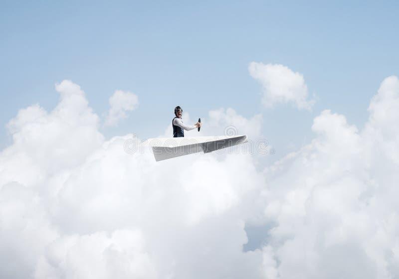 Hombre de negocios en el sombrero del aviador que se sienta en el avi?n del papel fotos de archivo libres de regalías